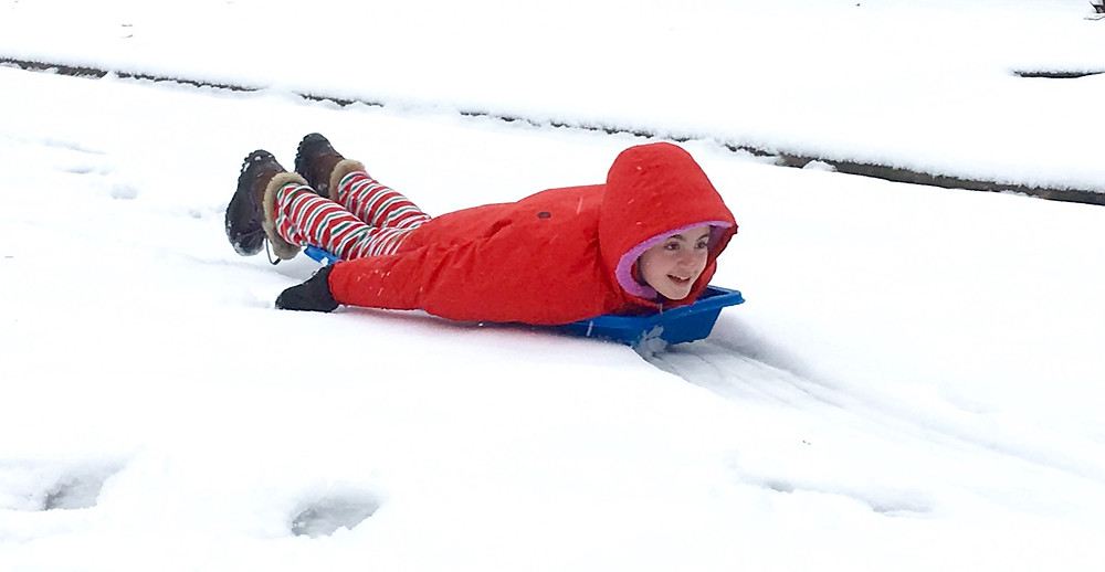 Image of a child sledding down a snowy hill. Raleigh Psychotherapy, counseling, holidays, Katherine Broadway