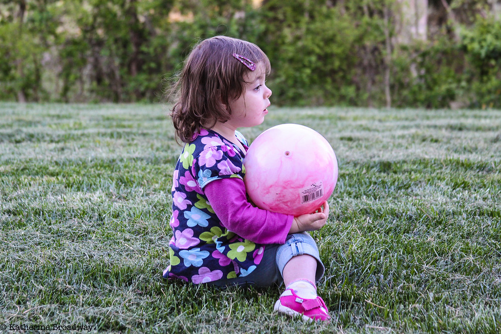 Image of toddler sitting on grass holding a large ball. Raleigh Psychotherapy, counseling, Overwhelmed, Broadway