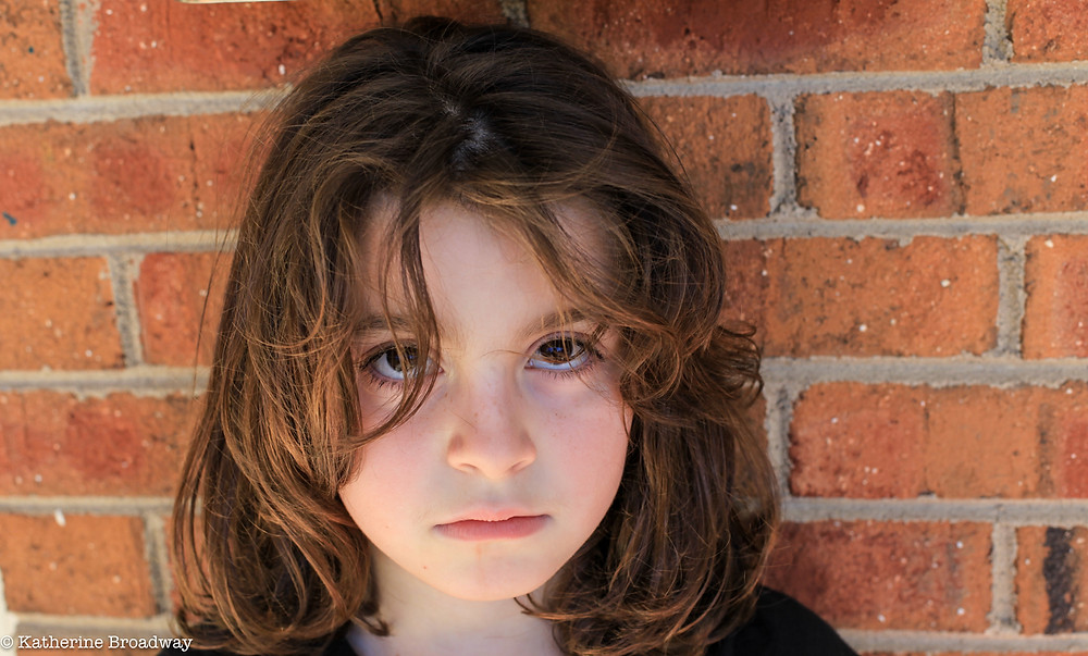 Image of young girl standing against brick wall looking unhappy. Raleigh Psychotherapy, counseling, The Value of Being Told No