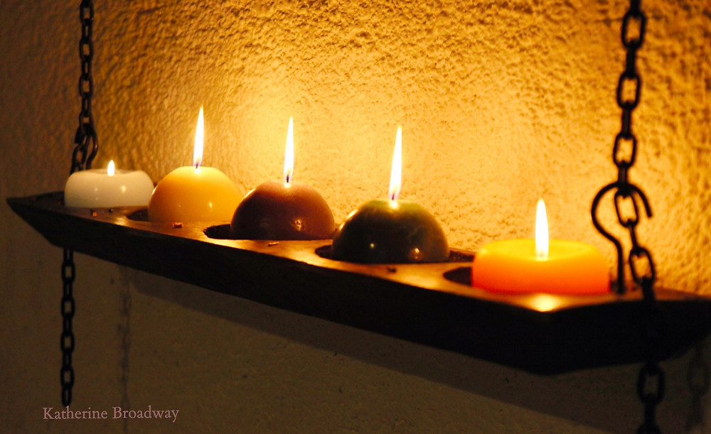 Image of 5 candles burning on a wooden shelf. Raleigh Psychotherapy, counseling,Winter Solstice, Katherine Broadway