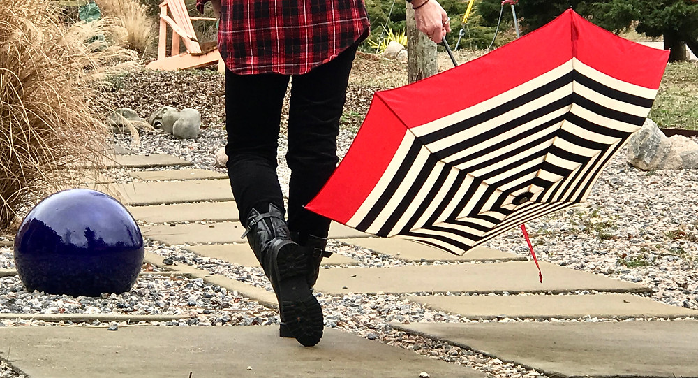 Image of a person walking down a stone path, carrying a red, white, and black umbrella. Raleigh Psychotherapy, counseling, Katherine Broadway, Mdiv, LPC