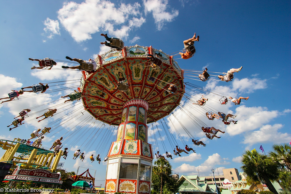 Image of ride at a fair, people in chairs swinging around high in the air. Raleigh Psychotherapy, counseling, distraction, Katherine Broadway