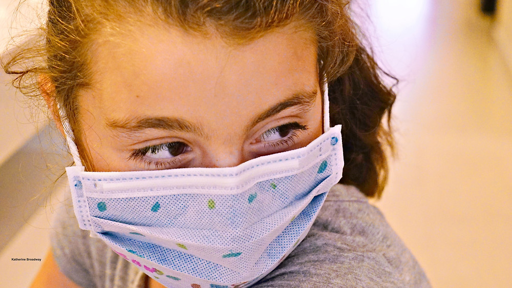 Image of a girl wearing a surgical mask. Raleigh Psychotherapy, counseling, Emotional Contagion, Katherine Broadway