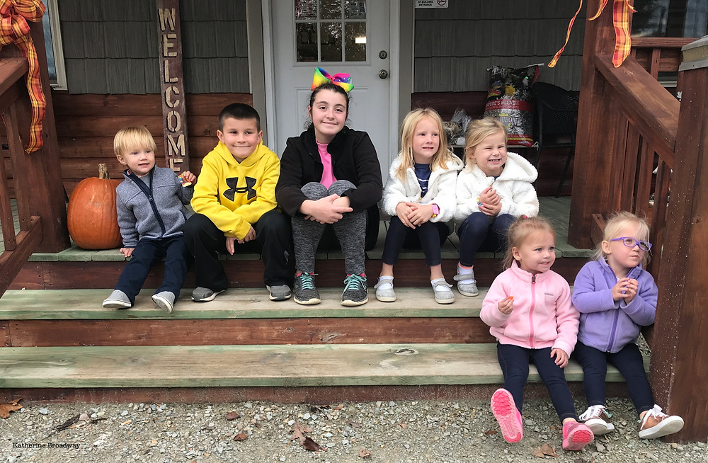 Image of 6 toddlers sitting on steps with a teen girl. Raleigh Psychotherapy, counseling, loneliness, Katherine Broadway