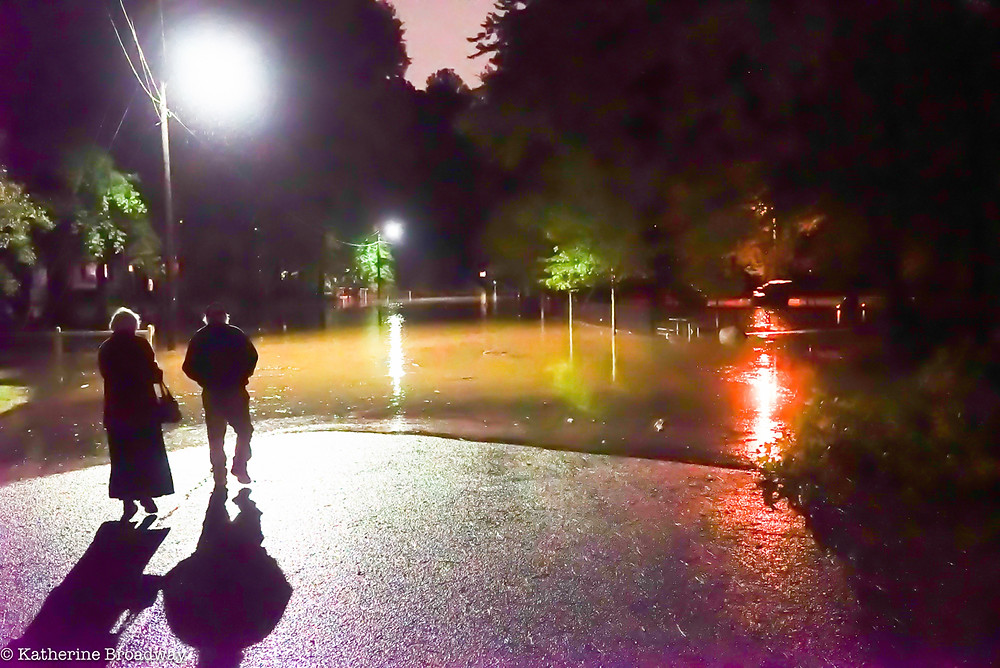 Image of two people walking into flooded street after hurricane Matthew, counseling, psychotherapy, Katherine Broadway