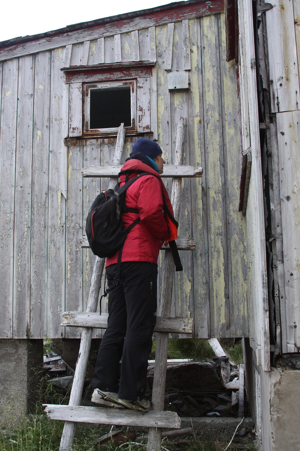Photo of old wood building and person in red winter jacket.  © Katherine Broadway | Find your true self