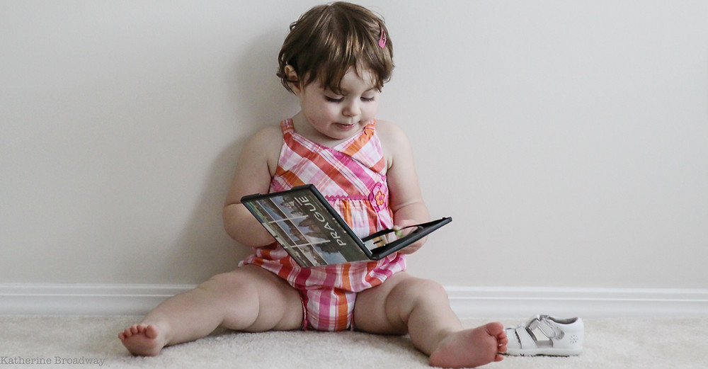Image of a toddler sitting on the floor holding a CD case. Raleigh Psychotherapy, counseling, New Story, Katherine Broadway