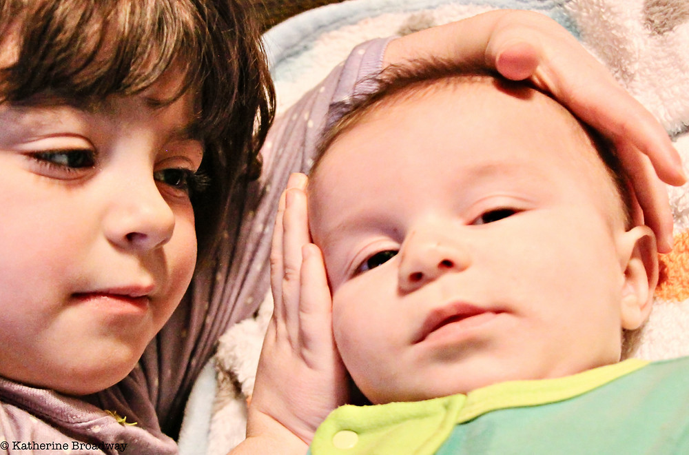 Image of young child holding face of a newborn. Raleigh Psychotherapy, counseling, Mind, Katherine Broadway