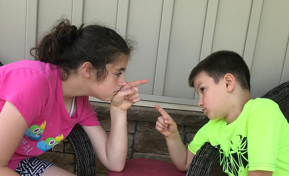 Image of young siblings points fingers at each other. Raleigh Psychotherapy, counseling, blame, Katherine Broad