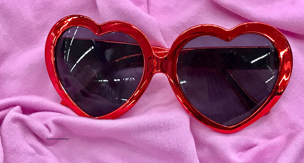 Image of red heart shaped sun glasses on pink cloth. Raleigh Psychotherapy, counseling, Elton John, Rocketman, Katherine Broadway