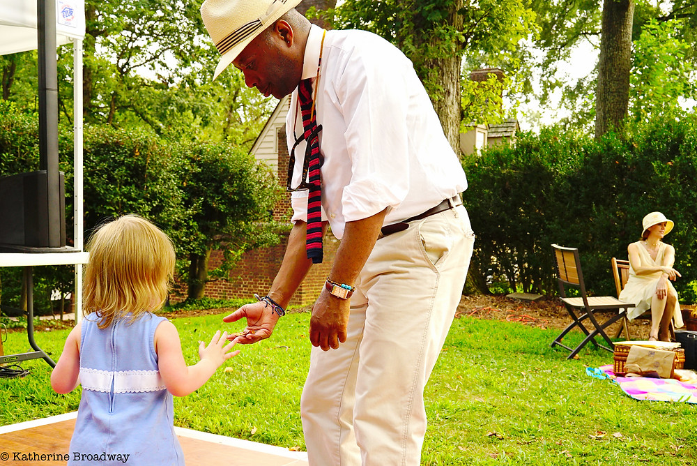 Image of small white child touching older black gentleman's hand.Raleigh Psychotherapy, counseling, emotional intelligence