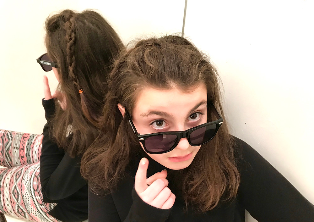 Image of a teen girl sitting against a mirror, looking over the top of her sunglasses. Raleigh psychotherapy, counseling, Katherine Broadway