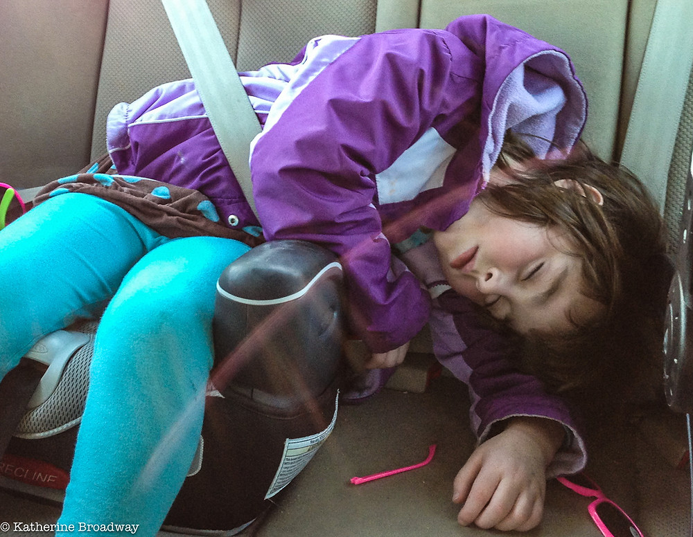 Image of sleeping girl belted in car seat,