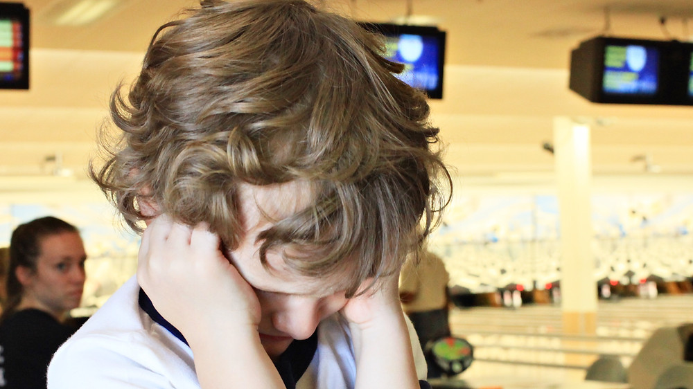 Image of child in bowling alley covering his ears to block the noise. Raleigh Psychotherapy, counseling, Memory, Katherine Broadway