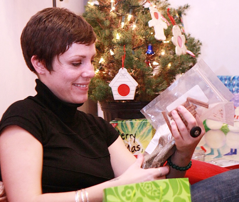 Image of young woman  holding a toy near a Christmas tree.Raleigh Psychotherapy, counseling, Katherine Broadway, holidays