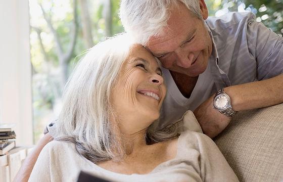 Senior couple hugging and smiling on sofa debt free no financial worries Paisley UK