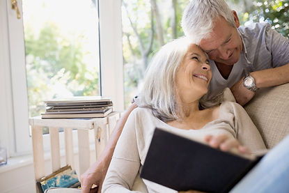 A female senior is seated leaning onto the back of a couch with a book on her lap. A male senior is behind the couch, leaning foward to touch his head with the lady's head. They are both smiling.  bo