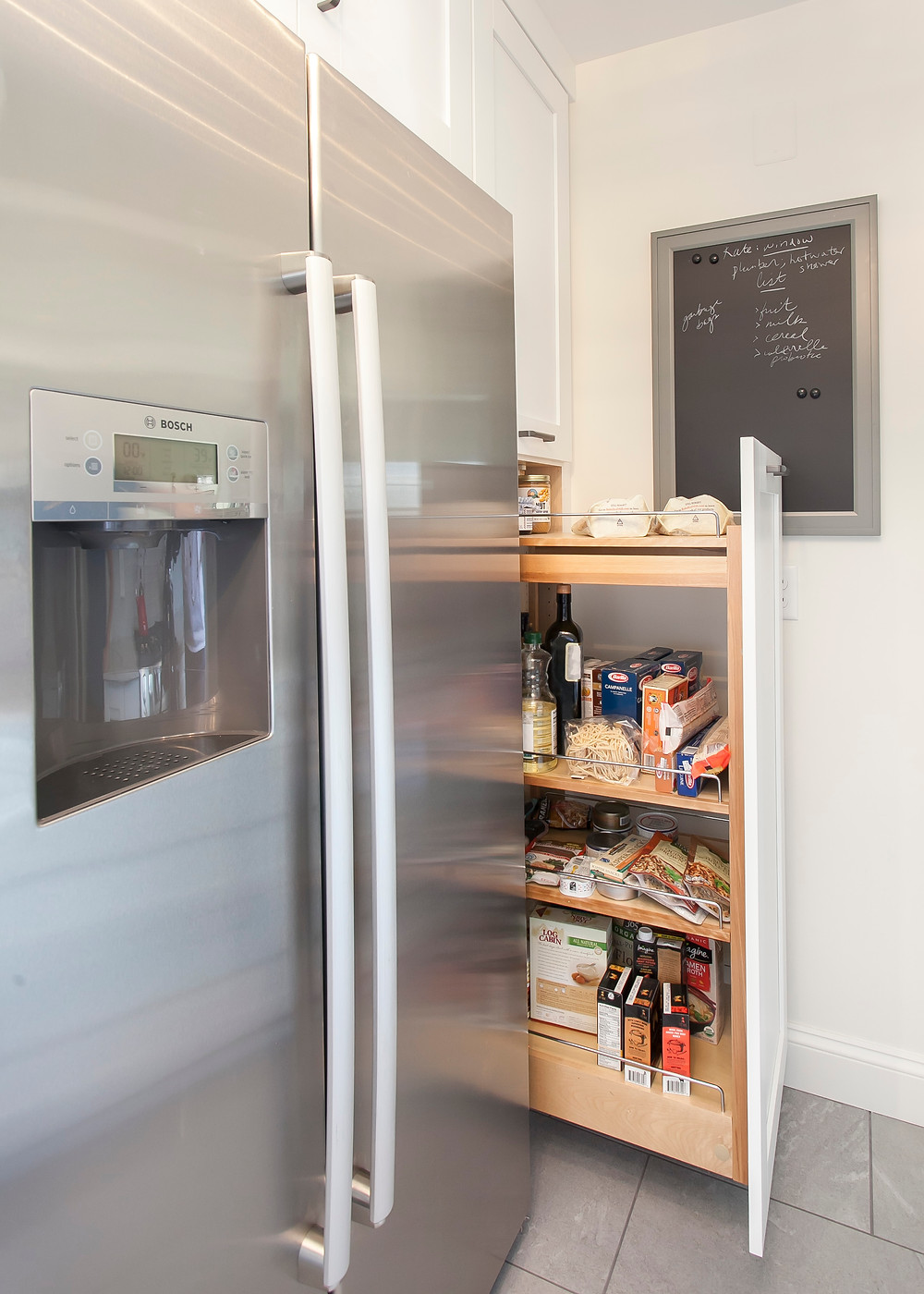 Small kitchen refrigerator and pantry cabinet.
