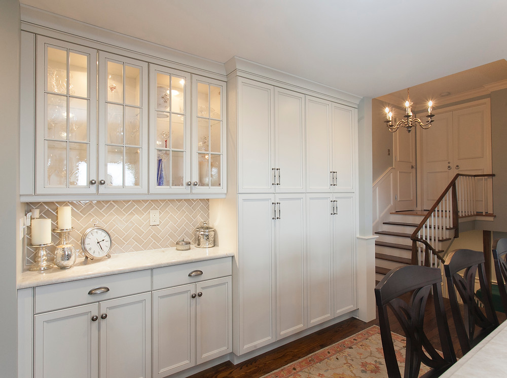 Floor to ceiling pantry cabinets and glass front wall cabinets.