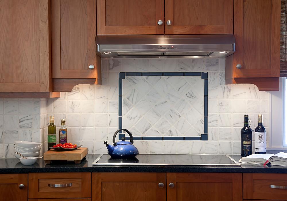 Induction cooktop wood cabinetry decorative backsplash