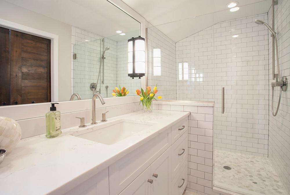 White bathroom with quartz countertops and subway tile