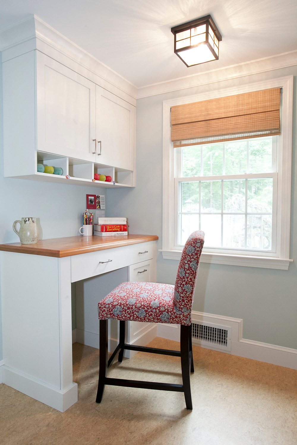 Built-in desk in white kitchen with wood top