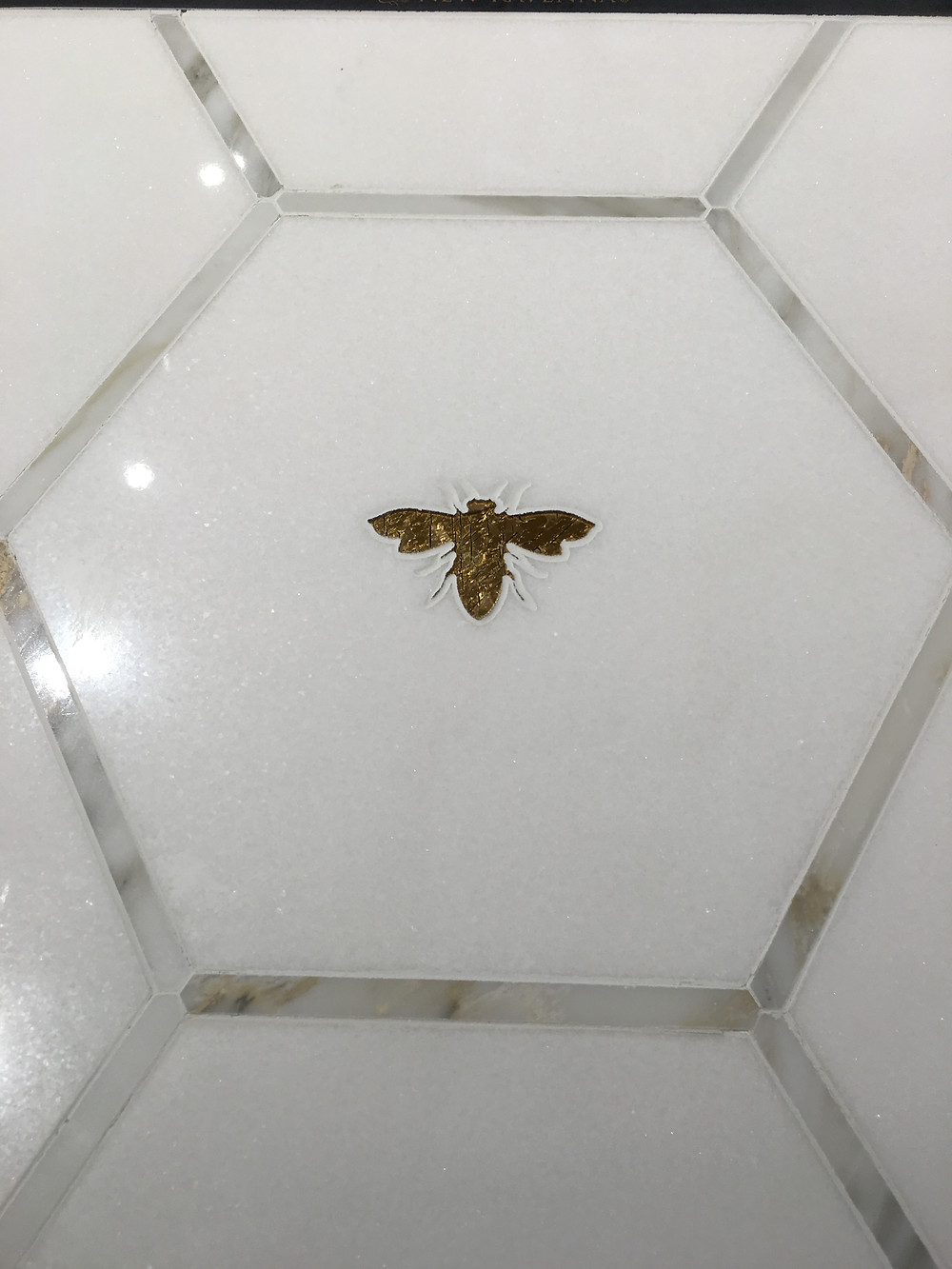 Honeycomb shaped tile complete with inlaid stone bee.
