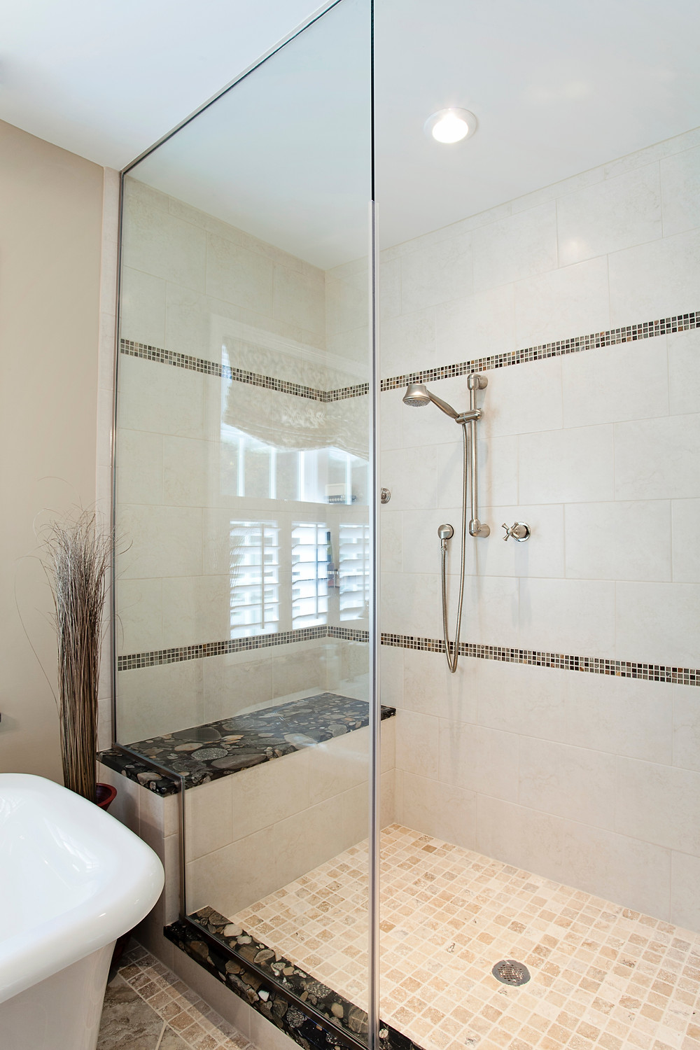Large shower with bench and glass panel