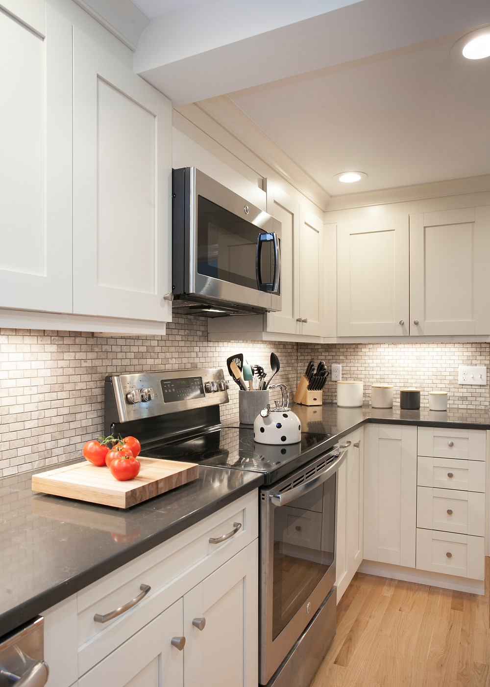 White kitchen with black countertops and stainless steel appliances