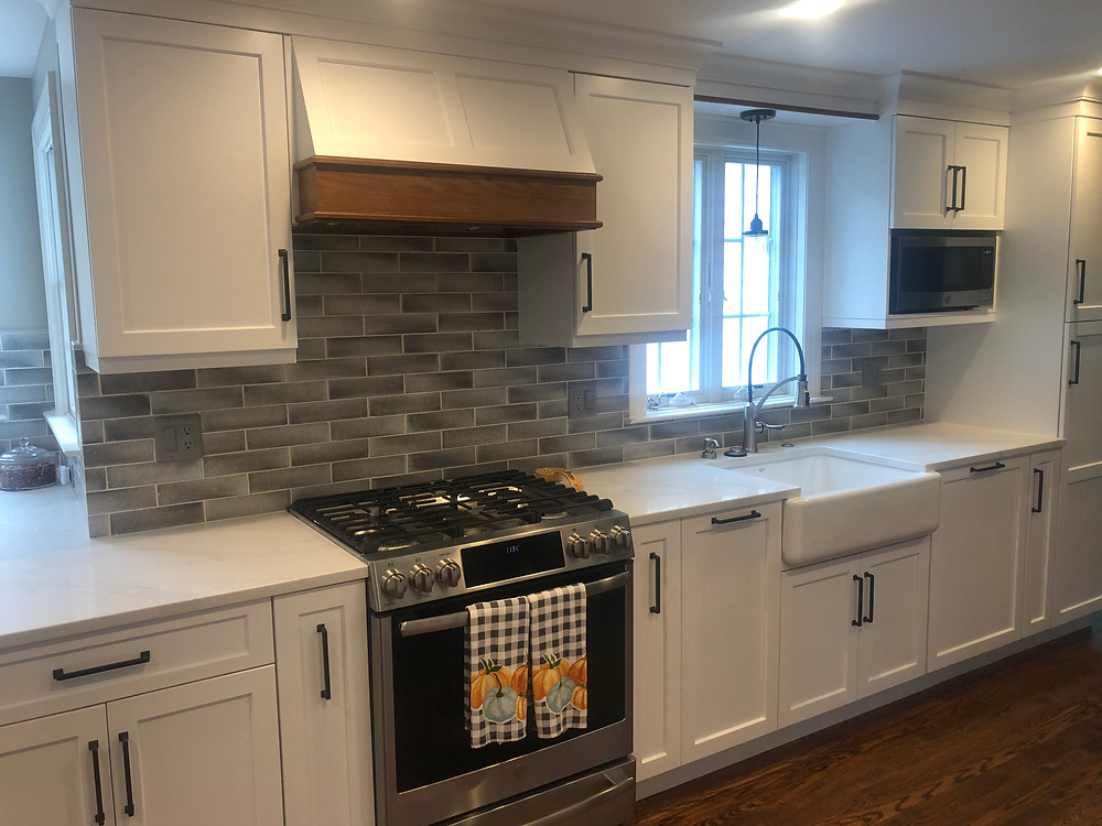 White kitchen with custom hood wood accent