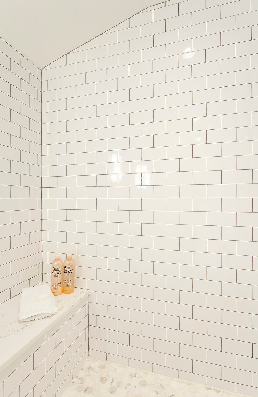 Classic subway tile with dark grout, marble floor and shower bench seat