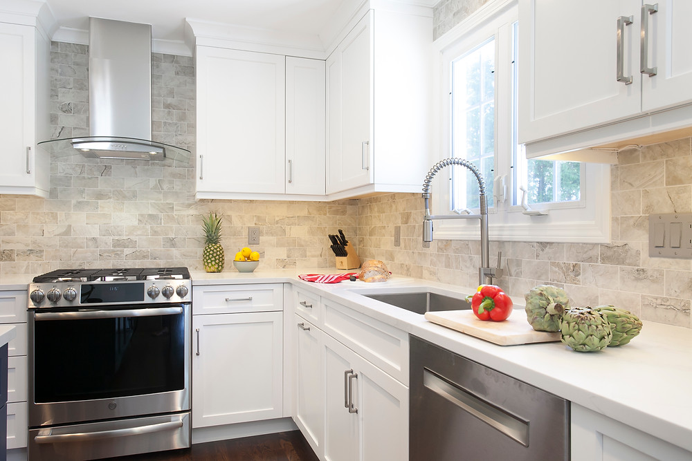 White kitchen with white quartz countertops and stainless steel appliances