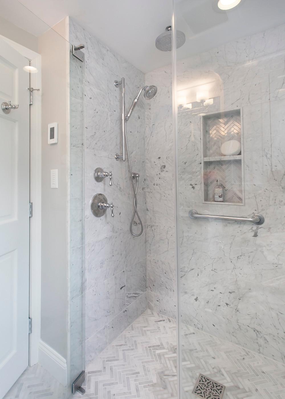 Curbless shower with herringbone marble floor