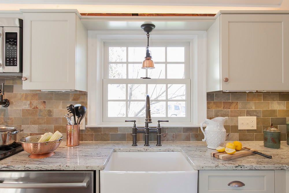 White kitchen cabinetry with slate backsplash