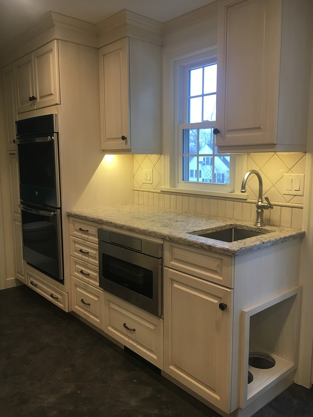 Off white kitchen with prep sink and dog feeding station