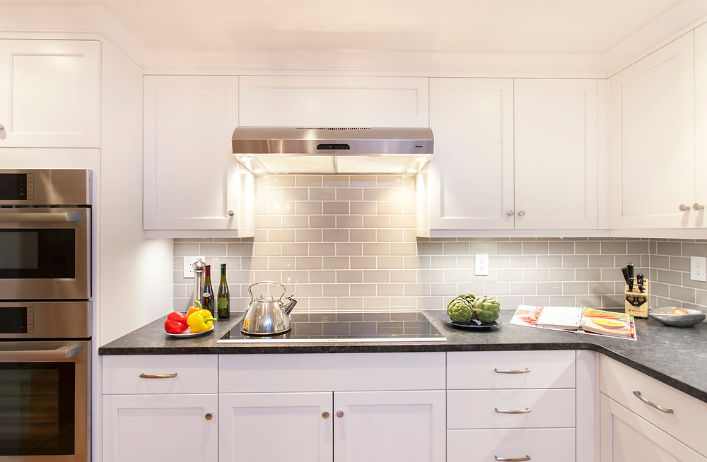 White kitchen induction cooktop double ovens subway tile