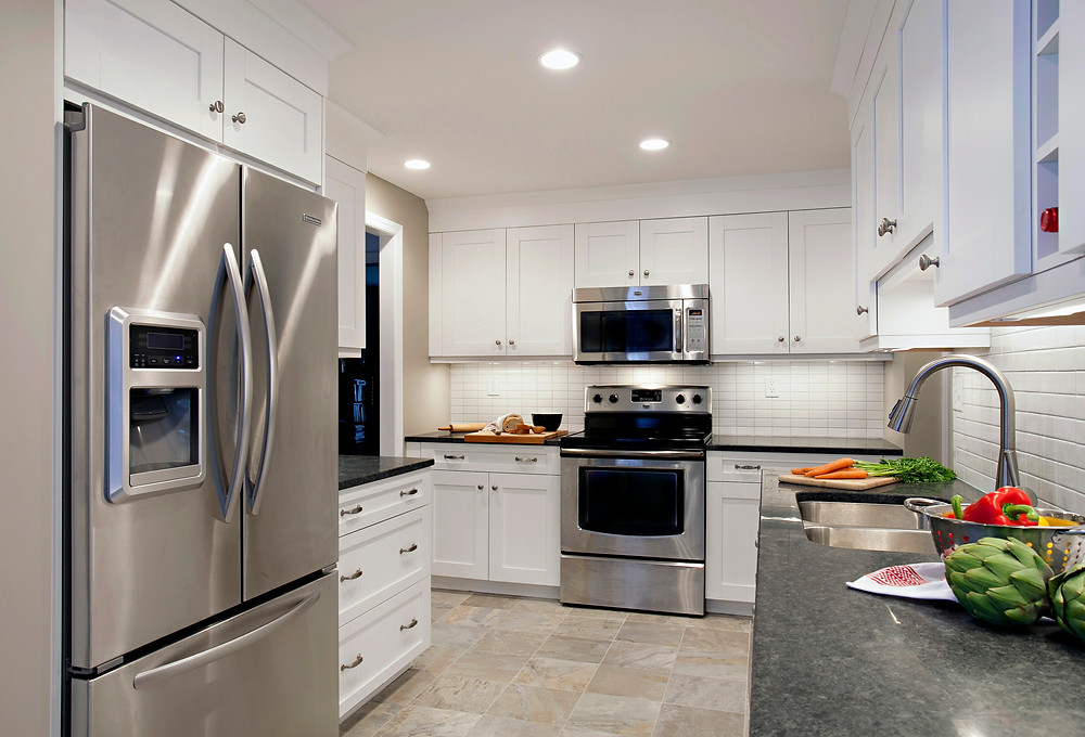White kitchen with stainless appliances and black countertops