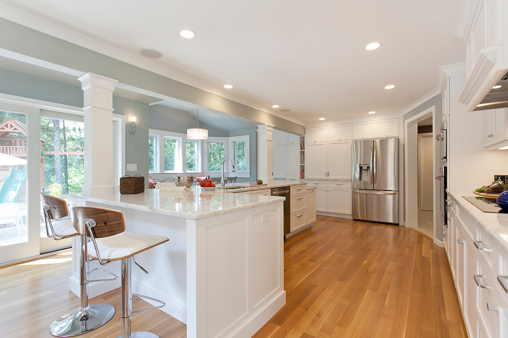 Large, luxury kitchen with white cabinets and stainless appliances
