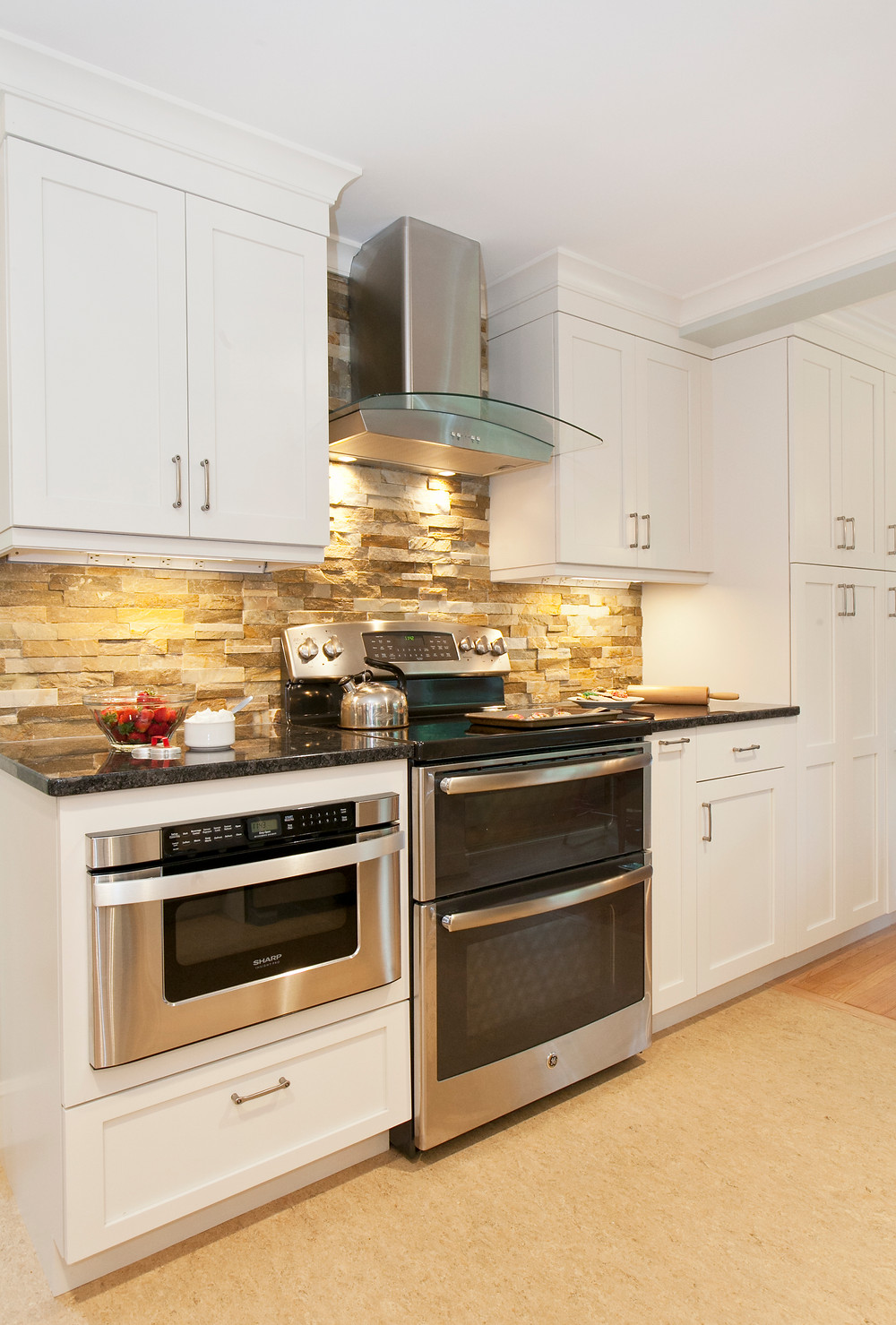 White kitchen cabinetry and stone backsplash
