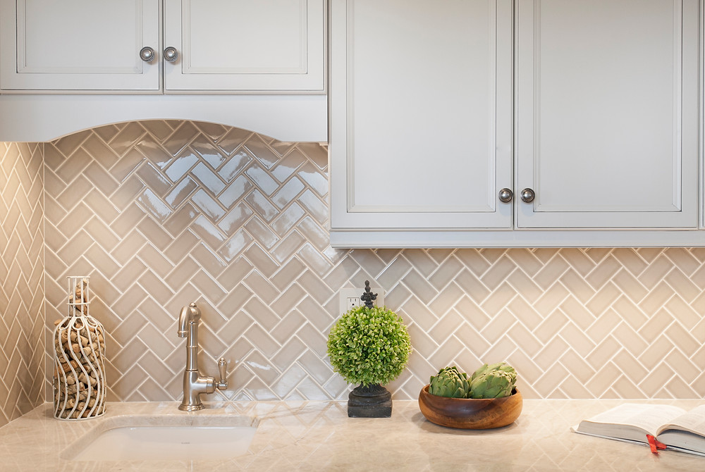White kitchen with wet bar and herringbone backsplash