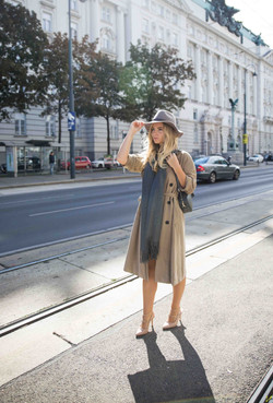 Model wearing a trench coat and hat