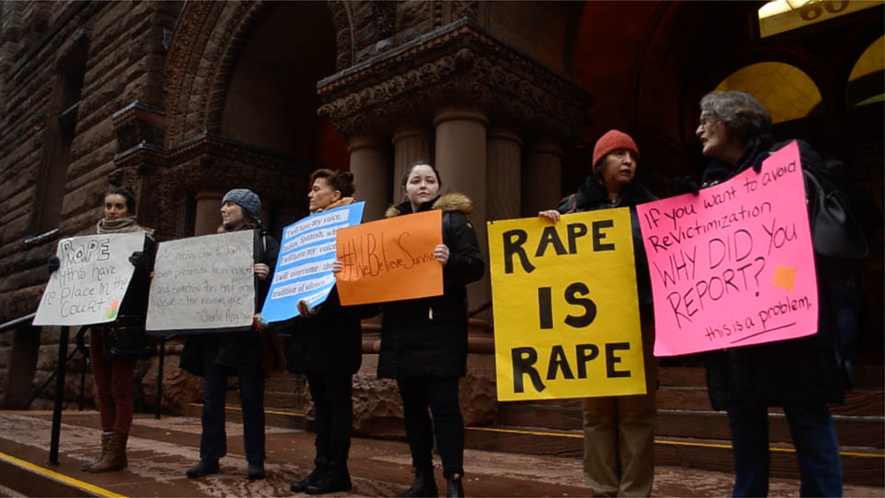 "Six protestors with signs protesting ""Rape is Rape"" ""We believe Survivors"" ""If you didn't want to be re-victimized - why did you report?"""
