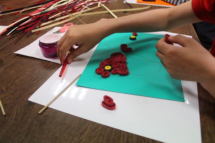 Bērni veido papīra kolāžas no papīra strēmelītēm