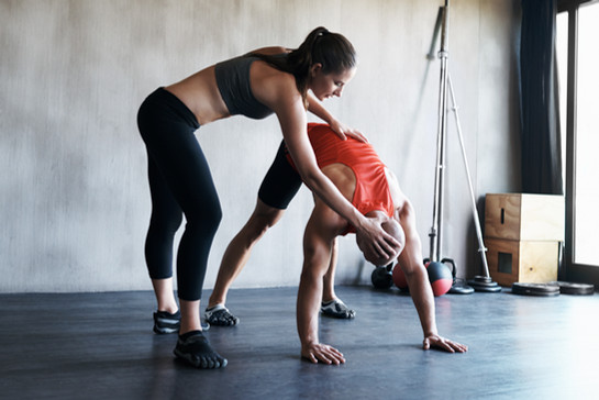 Trainer helping mobilize a client