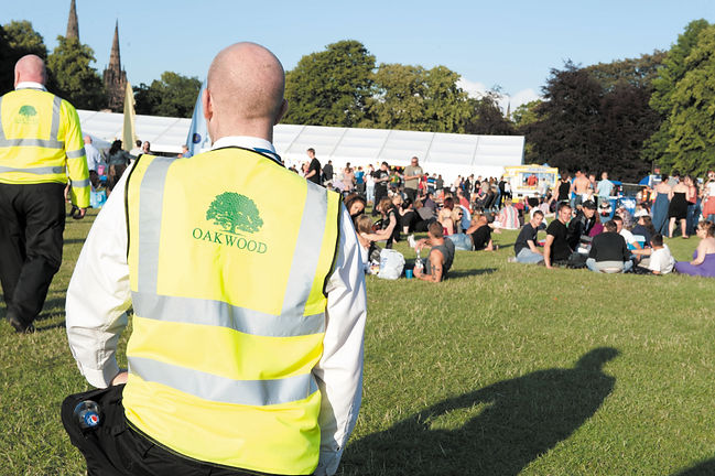 Employee wearing an Oakwood Security Solutions vest during an event in Midlands