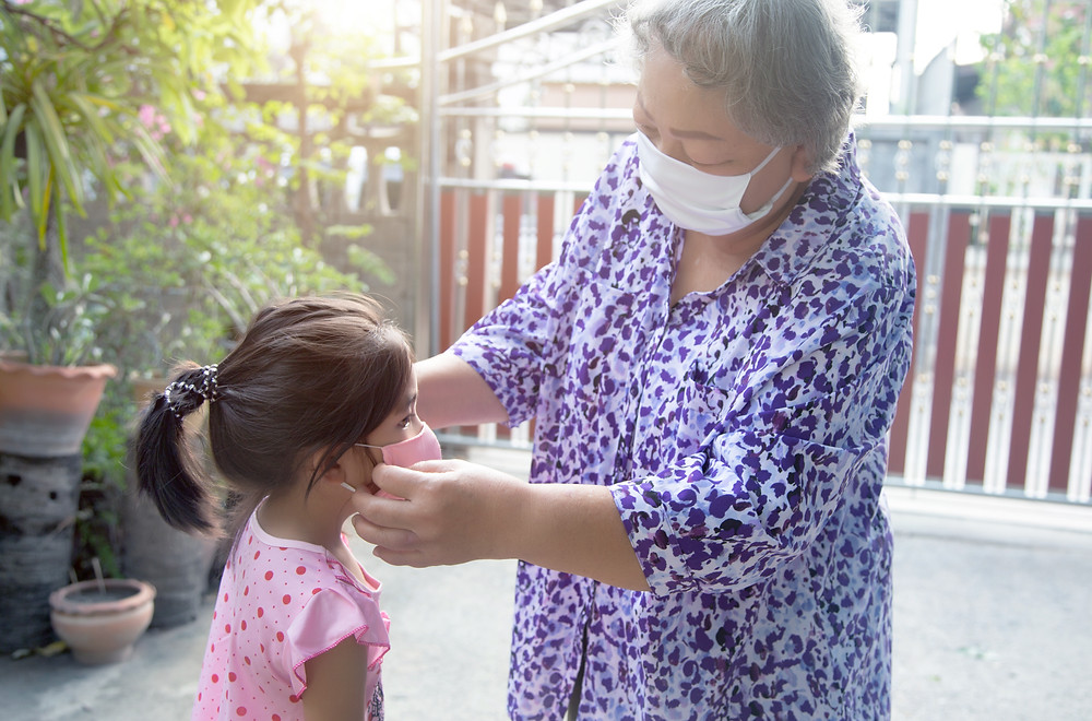 Grandmom adjusting mask of her child.