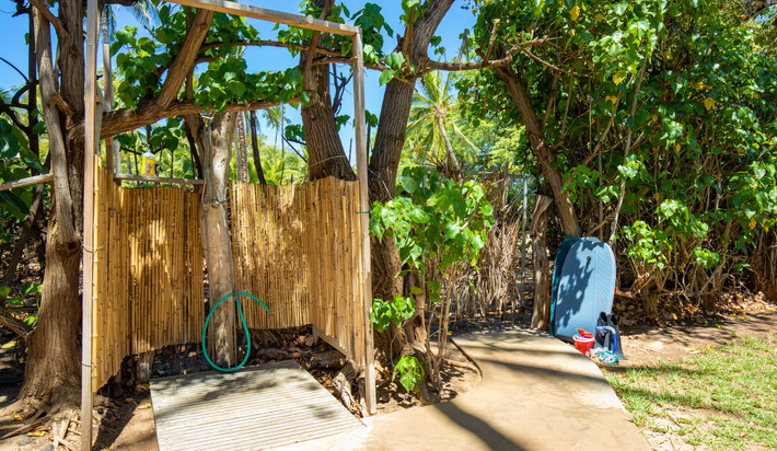Outdoor shower with hot and cold water. Beach gate is located next to it and leads to the sandy beach