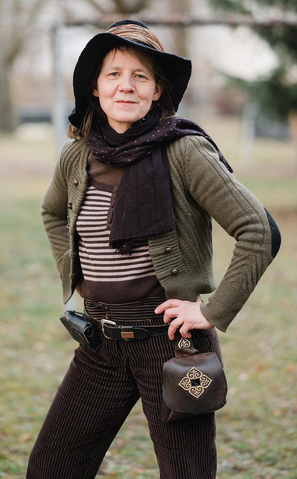 Auf dem Bild ist Birgit zu sehen, die einen Hut trägt, einen Schal und eine olivgrüne Strickjacke, ein gestreiftes Oberteil und eine schwarze Hose. Um die Hüfte trägt sie eine Tasche aus Leder.