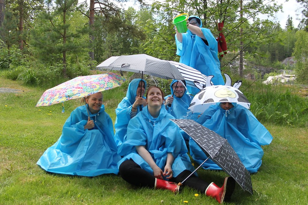 5 actives of HUMAKO sit under umbrellas, when one pours water on them.