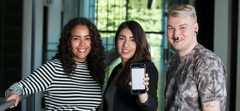 Three students holding a mobile phone.